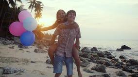 Förälskade par har roliga hållande mångfärgade ballonger att rotera omkring har att tycka om semester på den tropiska stranden un stock video