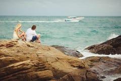 Förälskade par sitter på den steniga stranden nygifta personer som ser det övergående fartyget Arkivbild