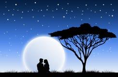 Förälskade par tycka om månen Arkivbild