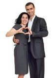 Förälskade romantiska par, den iklädda svarta dräkten, showhjärtaform från händer, isolerade vit Arkivfoton