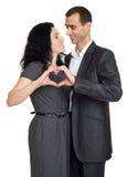 Förälskade romantiska par, den iklädda svarta dräkten, showhjärtaform från händer, isolerade vit Fotografering för Bildbyråer