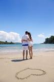 Förälskade romantiska par har gyckel på stranden med hjärtadrawi Royaltyfri Fotografi