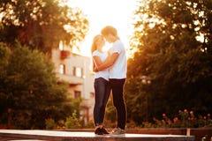 Förälskade tyckande om ögonblick för par under solnedgång royaltyfria bilder