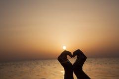 Förälskade tyckande om mjuka ögonblick för flicka på solnedgången under feriewi Arkivbilder