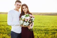 Förälskade unga lyckliga par, flickainnehavblommor som, är lyckliga och, tycker sig om företaget för ` s, advertizingen och utsav Royaltyfri Bild