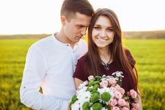 Förälskade unga lyckliga par, flickainnehavblommor som, är lyckliga och, tycker sig om företaget för ` s, advertizingen och utsav Arkivbild