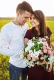 Förälskade unga lyckliga par, flickainnehavblommor som, är lyckliga och, tycker sig om företaget för ` s, advertizingen och utsav Arkivbilder