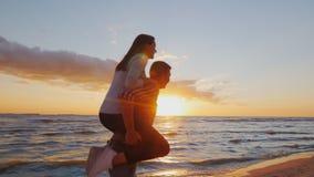 F?r?lskade unga par ha gyckel p? stranden p? solnedg?ngberugien En flicka sitter p? skuldrorna av m?n som k?r p? stranden arkivfilmer