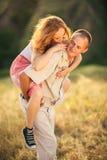 Förälskat bedra för gladlynta par på den gröna vårängen flicka Arkivfoton