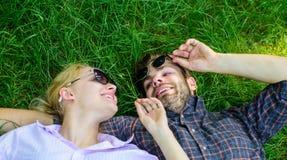 Förälskat enigt för par med naturen Naturen fyller dem med friskhet och inspiration Den orakade mannen och flickan lägger på gräs arkivfoto