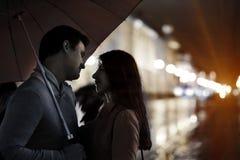 Förälskat gå för par i regnet Arkivfoto