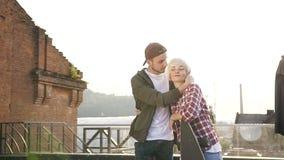 Förälskat gå för unga charmiga par med skateboarder på taket av en modern byggnad för terrass på solnedgången Grabben lager videofilmer