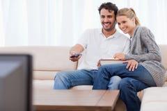 Förälskat koppla ihop hållande ögonen på TVstunder som äter popcorn Arkivfoto