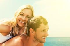 Förälskat krama för lyckliga par och skratta på stranden Royaltyfri Foto