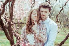 Förälskat krama för unga stilfulla lyckliga par i blommande trädgård Pojke och flicka som utomhus vilar arkivfoto