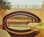 Förälskat kyssa för par under en bro Arkivbilder