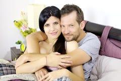 Förälskat le för härliga lyckliga par som kramas i säng Arkivfoton