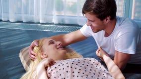 Förälskat ligga för lyckliga unga par på golv i solbelyst rum och kyssa lager videofilmer