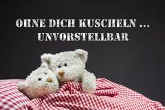 Förälskat ligga för två beige nallebjörnar i säng. Arkivfoton