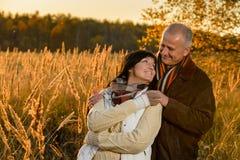 Förälskat omfamna för par i höstsolnedgång royaltyfria foton