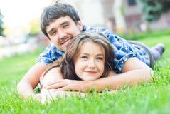Förälskat omfamna ligga för lyckliga par utomhus Arkivfoto