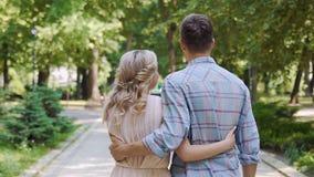Förälskat parkerar gå för ung man och för kvinna i sommar, den tillbaka sikten, ultrarapid lager videofilmer