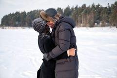 Förälskat parkerar omfamna för unga millennial par i vinter utomhus- arkivbild