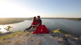 Förälskat sammanträde för par på flodkanten Solnedgången tänder lager videofilmer