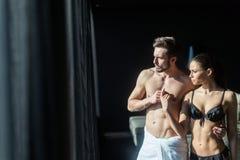 Förälskat se för idrotts- par utanför till och med fönstret av a Royaltyfri Bild