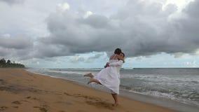 Förälskat virvla för unga par och krama på havstranden på solnedgången stock video