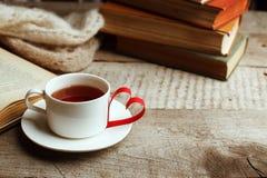 Förälskelse av böcker som läser Bunt av böcker på trätabellen och origamipapper tillverkar formen av en hjärta, kopp te Arkiv, royaltyfri foto