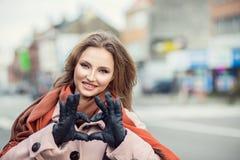 Förälskelse Closeupstående som ler det lyckliga för danandehjärta för ung kvinna tecknet, symbol med händer Arkivbild