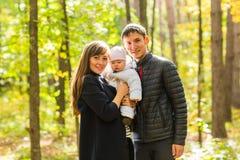 Förälskelse, föräldraskap, familj, säsong och folkbegrepp - le behandla som ett barn par med nyfött i höst parkerar Arkivbild