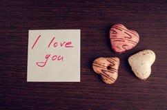 Förälskelse för anmärkning I dig med kakor på träbakgrund Arkivbild