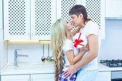 Förälskelse för dag för St-valentin` s 14 Februari Stilig ung man som hemma ger gåva till den härliga kvinnan i köket Arkivbild