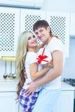 Förälskelse för dag för St-valentin` s 14 Februari Stilig ung man som hemma ger gåva till den härliga kvinnan i köket Royaltyfri Foto