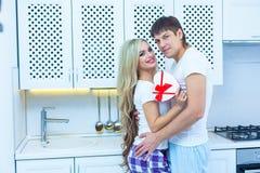 Förälskelse för dag för St-valentin` s 14 Februari Stilig ung man som hemma ger gåva till den härliga kvinnan i köket Royaltyfri Fotografi