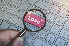 Förälskelse för skriftligt ord på den röda knappen för tangentbord som beskådas till och med förstoringsglaset Stäng sig upp av d fotografering för bildbyråer