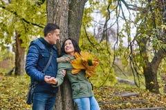 Förälskelse-, förhållande-, familj- och folkbegrepp - le par som kramar i höst, parkera Arkivbilder