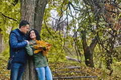 Förälskelse-, förhållande-, familj- och folkbegrepp - le par som kramar i höst, parkera Royaltyfri Bild