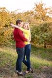 Förälskelse, förhållande, säsong, kamratskap och folkbegrepp - lycklig man och kvinna som tycker om guld- höstnedgångsäsong med p Arkivfoto