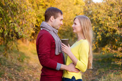 Förälskelse, förhållande, säsong, kamratskap och folkbegrepp - lycklig man och kvinna som tycker om guld- höstnedgångsäsong med p Royaltyfria Foton