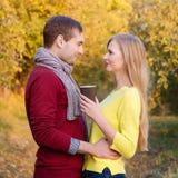 Förälskelse, förhållande, säsong, kamratskap och folkbegrepp - lycklig man och kvinna som tycker om guld- höstnedgångsäsong med p Fotografering för Bildbyråer