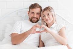 Förälskelse, folk och begreppet av lycka - le par i säng, händer som gör en hjärta för att forma arkivbild