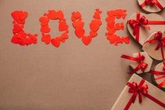 Förälskelse från hjärtor och stilfulla gåvor med röda band Arkivfoto