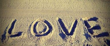 FÖRÄLSKELSE i sanden av stranden royaltyfri fotografi