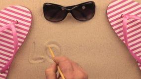 Förälskelse inskrift som är skriftlig vid handen på sanden, bland strandtillbehör Tecken- och symbolrekreation stock video
