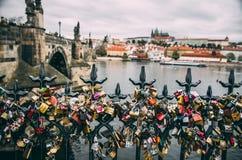 Förälskelse- och förbindelsehänglås på den Prague bron Arkivfoton