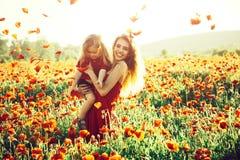 Förälskelse och familj, lycklig moder och barn i vallmofält royaltyfria bilder