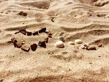 FÖRÄLSKELSE- och HJÄRTAdiagram på en sand Arkivfoto